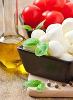 Mozzarella, Tomaten und frische Basilikumblätter auf hölzernem Hintergrund foto