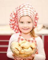 lächelndes kleines Mädchen in der Kochmütze, die Schüssel mit Keksen hält foto