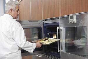 männlicher Koch, der Backblech in Ofen legt foto