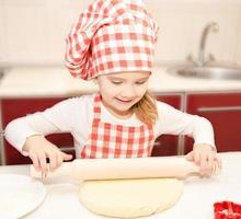 lächelndes kleines Mädchen mit kochendem Hut, der Teig rollt