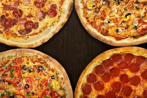 vier Pizza auf einem dunklen hölzernen Hintergrund foto