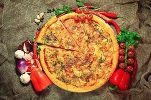 Pizza mit rustikalem Hintergrund von Gemüse und Kräutern foto