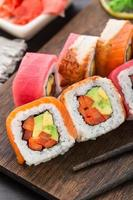Regenbogen-Sushi-Rolle mit Lachs, Thunfisch und Aal foto