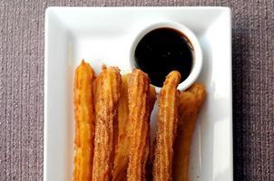 spanische Donut-Churros mit dunkler Schokoladen-Dip-Sauce foto