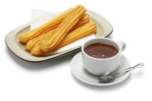 Churros und heiße Schokolade auf weißem Hintergrund foto