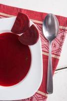 Borschtschsuppe mit frischem Rosmarin in weißem Teller foto