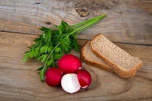 frische rote Rettichpetersilie und Brot auf alter Holzoberfläche foto