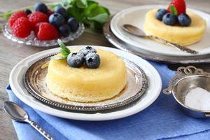 leckerer Zitronenpuddingkuchen mit Beeren serviert foto