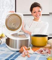 Frau kocht mit Multicooker