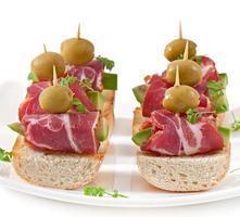 Snack auf Toast mit Schinken, Avocado und Oliven foto