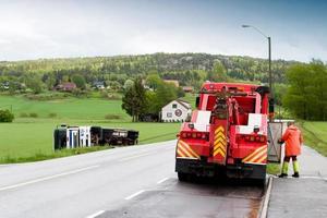 ein roter Abschleppwagen, der die Autobahn einer ländlichen Stadt säubert foto