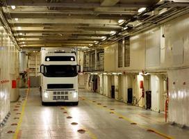 weißer LKW auf Frachtdeck der Fähre foto
