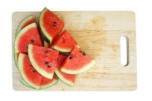 geschnittene Wassermelonen auf Holzteller, lokalisiert auf weißem Hintergrund