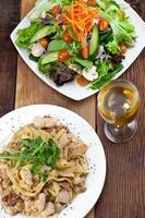 Hühnernudeln und Gemüsesalat Mahlzeit auf dem Tisch foto
