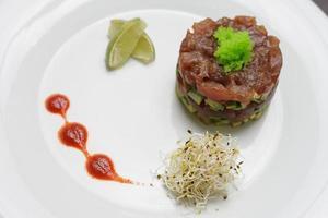 Lachs mit Sauce Tartar und Limette auf einem einfachen weißen Teller foto