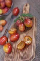 frisch gepflückte Pflaumen mit den Blättern auf einem Holzbrett foto
