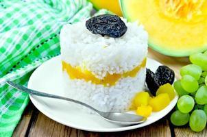 Reis mit Kürbis und Trauben auf dem Brett foto