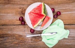 Wassermelonenscheiben auf dem Teller als nächstes mit Pflaumen