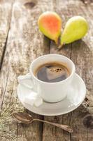 Kaffeetasse schwarz Holzbrett braune Birnen weiß