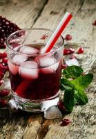 frischer roter Saftcocktail mit Granatapfelkernen, Minze und Eis foto