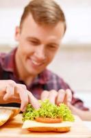 Nahaufnahme des Mannes, der Brot mit Salat verziert foto
