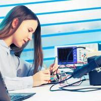 Mädchen, das elektronisches Gerät auf der Leiterplatte repariert foto