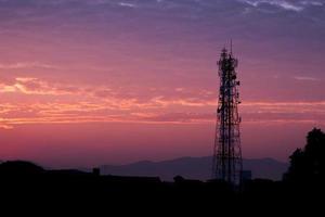 Silhouetten Telekommunikationsturm bei Sonnenaufgang und Dämmerungshimmel.