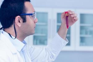 Wissenschaftsstudent hält Fläschchen hoch foto