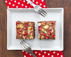 Schokoladenkuchen mit Granatapfel und Mandel dekoriert foto