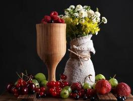 Stillleben mit Beeren und Blumen auf dunklem Hintergrund foto