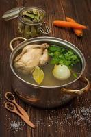 Hühnerbrühe mit Gemüse und Gewürzen in einem Topf foto