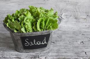 frischer grüner Blattsalat in einem Weinleseeimer foto