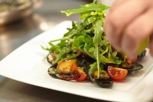 Salat mit Muscheln auf einem weißen Teller foto