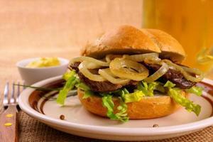Gegrilltes Rindfleisch mit Zwiebelringen in Brötchen und Bier foto