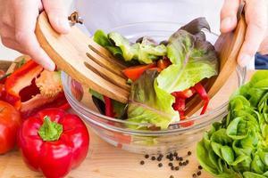 Mann, der gesunden Salat zubereitet foto