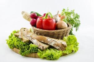 Komposition mit Brot und Gemüse auf Holzbrett.