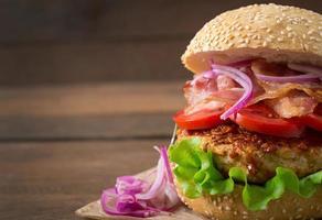 großes Sandwich - Hamburger Burger mit Rindfleisch, roten Zwiebeln, Tomaten. foto