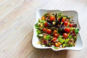 frischer Gemüsesalat mit Basilikumblättern in Keramikschale foto