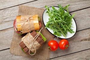 zwei Sandwiches mit Salat, Schinken, Käse und Tomaten