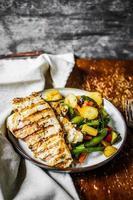gegrilltes Huhn mit gebackenem Gemüse auf rustikalem Hintergrund foto