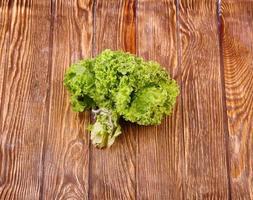 frische grüne Salatblätter auf einem dunklen hölzernen Hintergrund foto