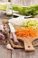 geschnittene Karotten, Zwiebeln und Sellerie auf einem Hackklotz foto