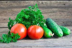 Tomate und Gurke mit vielen Arten auf einem hölzernen Hintergrund