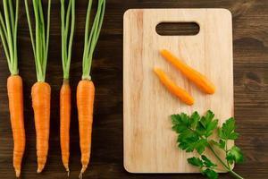 Bund frische Karotten mit grünen Blättern auf Holz foto