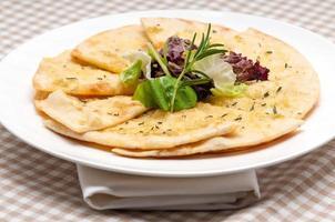 Knoblauch-Fladenbrot-Pizza mit Salat oben drauf