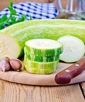 Zucchinigrün mit Knoblauch auf einem Brett foto