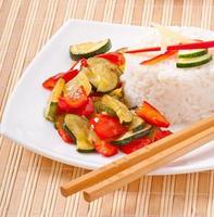 Teller mit gebratenem Gemüsereis und Essstäbchen.