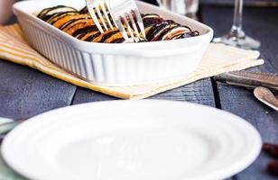 Ratatouille in weißem Auflauf und leerem runden Teller foto