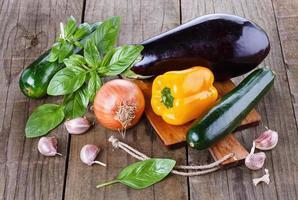 buntes frisches Gemüse und Kräuter über hölzernem Hintergrund foto