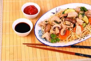 Hühnerfleisch mit chinesisch-asiatischen Nudeln, Gemüse foto